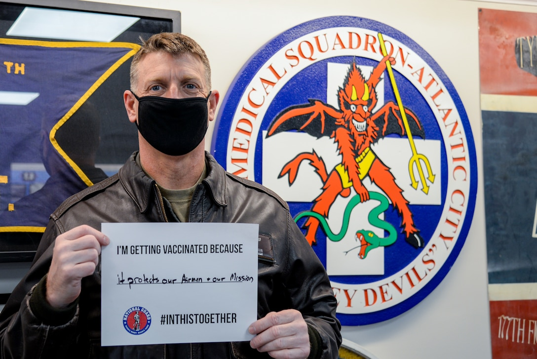 A photo of  Col. Bradford R. Everman holding a sign stating why he received one of the 30 COVID-19 vaccines given at the 177th Fighter Wing.