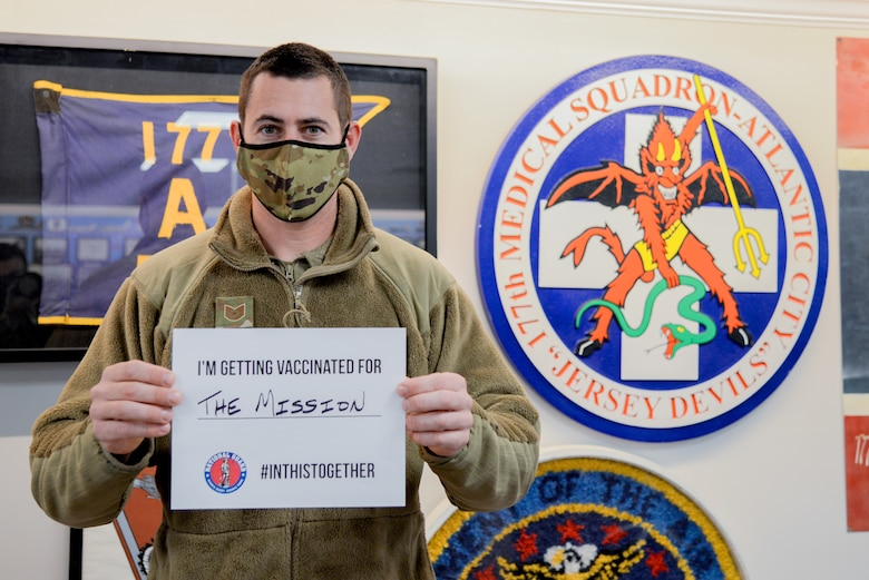 A photo of Tech. Sgt. Daniel J. Casaburi holding a sign stating why he volunteered to receive a COVID-19 vaccine