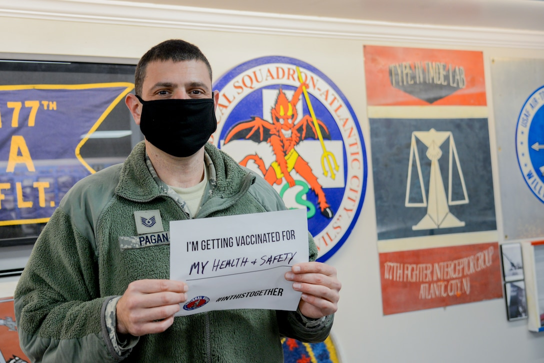 A photo of Tech. Sgt. Jason R. Pagan holding a sign stating why he volunteered to receive a COVID-19 vaccine.
