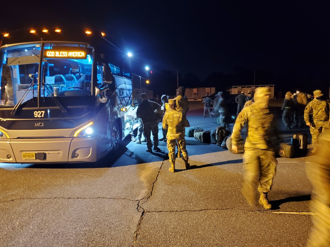 Before traveling to Washington D.C. to provide security, protect National Monuments, and ensure a peaceful transfer of power, members of the 177th Fighter Wing of the New Jersey Air National Guard load equipment and supplies onto a charter bus, Jan. 8, 2021, at the Atlantic City Air National Guard Base, N.J. New Jersey Air and Army National Guard members then processed through the Joint Reception, Staging, Onward movement, and Integration function with Joint Task Force 44, at the New Jersey National Guard Training Center, in Sea Girt, N.J. The JRSOI included a briefing, medical examinations and an administrative records review. (U.S. Air National Guard courtesy photo by Col. Aaron M. Dunn)