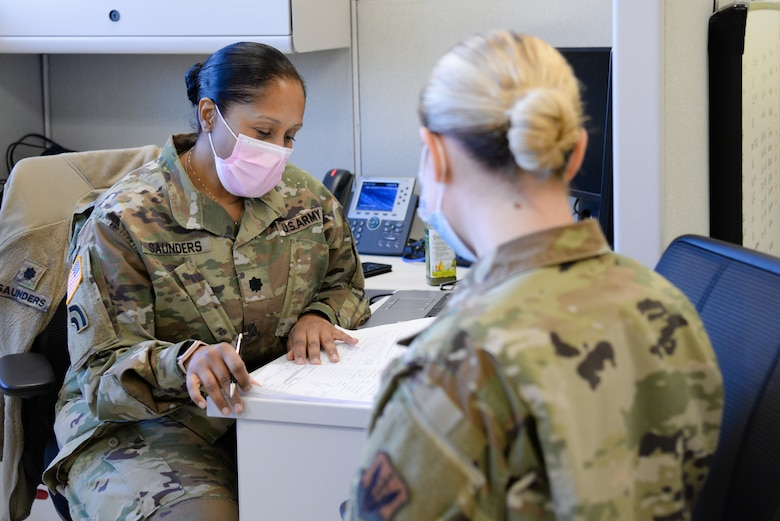 U.S. Army Lt. Col. Lorraine Saunders, 44th Infantry Brigade Combat Team brigadier surgeon, left, reviews the paperwork of U.S. Air Force Airman lauren A. Paduani, 177th Logistics Readiness Squadron traffic management office specialist, Jan. 13, 2021, at the New Jersey National Guard Base, Sea Girt, N.J. The out-process included a briefing, medical examinations and a sit-down with administration. (U.S. Air National Guard photo by Airman 1st Class Hunter Hires)