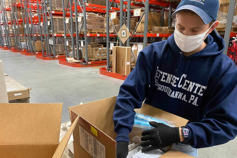 A man packs boxes with medical supplies.