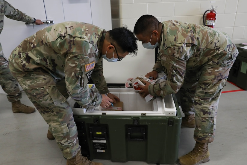 Two male servicemembers remove medical supplies from a cooler.