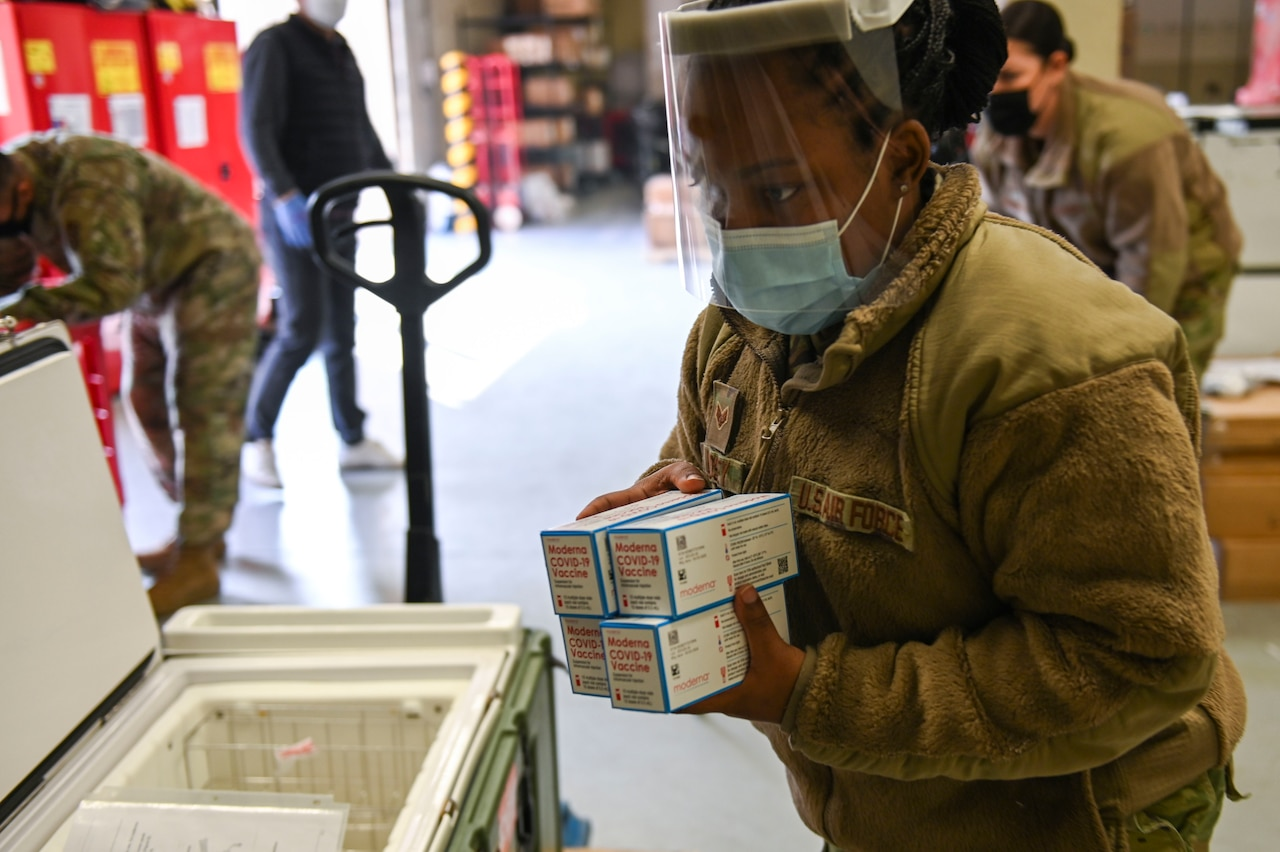 A female servicemember removes vaccines from a cooler.
