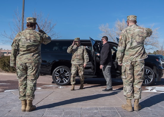 Two Delta 2 personnel salute Gen. James H. Dickinson as he exits his vehicle.