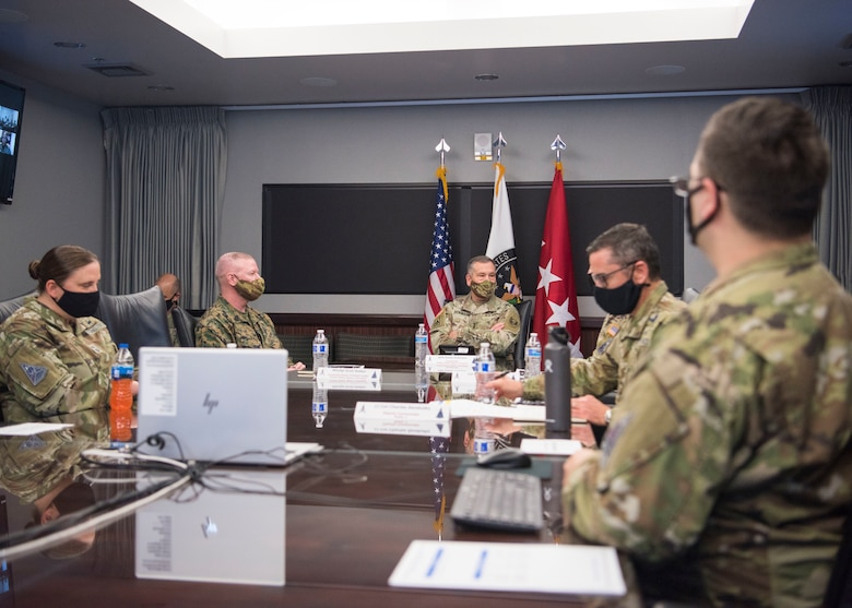 A group of U.S. Space Force personnel sit around a conference table during a briefing.
