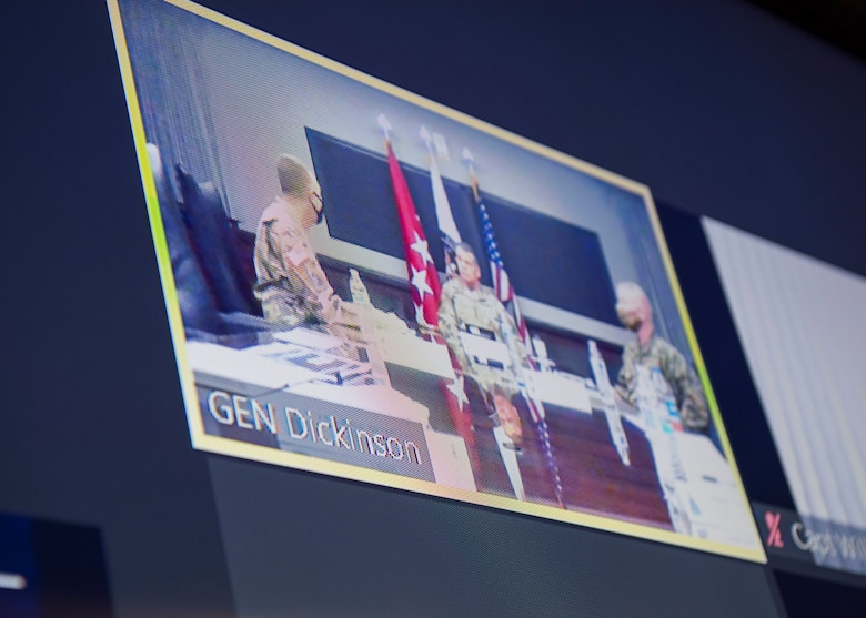 Picture of t.v. screen with video teleconference shot showing three military personnel sitting at a conference table.