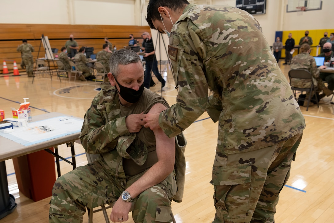 U.S. Air Force A1C Tyler Lancaster, 60th Healthcare Operations Squadron, medical technician, administers an initial COVID-19 vaccine to Col. Corey Simmons, 60th Air Mobility Wing commander, Dec. 29, 2020 at Travis Air Force Base, California. The vaccine requires two doses per person, separated by about four weeks between doses. It is designed to protect against the coronavirus, and officials are encouraging all prioritized personnel to take the vaccine as it becomes available. (U.S. Air Force photo by Airman 1st Class Alexander Merchak)