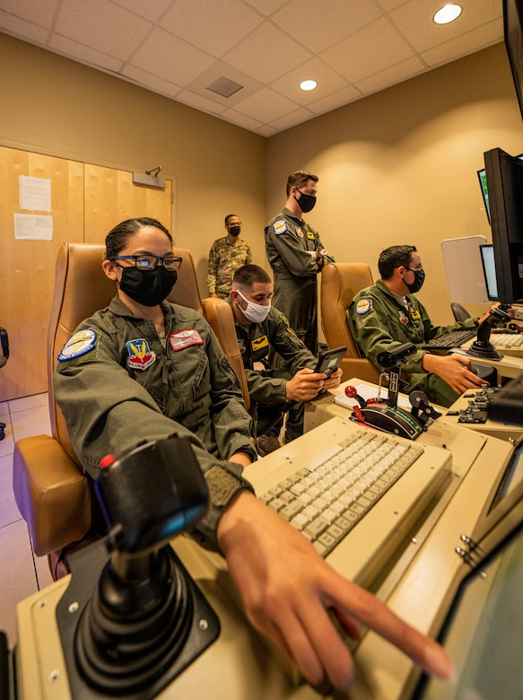 An airman points at one of her monitors before a sortie in a simulator.