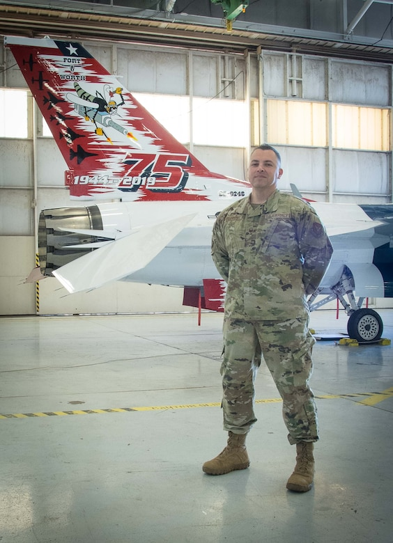 Master Sgt. David Flores, 301st  Fighter Wing Operations Group first sergeant, stands by the 301 FW F-16 heritage jet at U.S. Naval Air Station Joint Reserve Base Fort Worth, Texas on December 20, 2020. First Sgts. play a vital role to a wing's ability to accomplish their mission because they work directly with the Airmen in their respective squadrons. (U.S. Air Force photo by Jeremy Roman)