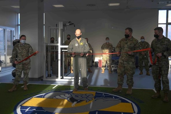 U.S. Air Force Brig. Gen. Jason E. Bailey, 31st Fighter Wing commander, participates in a ribbon-cutting ceremony at the Comprehensive Operational Medicine for Battle Ready Airmen (COBRA) Clinic with Airmen from the 31st Medical Group at Aviano Air Base, Italy, Jan. 14, 2021. The COBRA clinic is a newly innovated program unique to Aviano and designed to focus on readiness by preventing or reducing mental health and musculoskeletal profiles of our Airmen. The COBRA clinic is based on a hub and spoke model of care incorporating diagnosis, recovery, rehabilitation, and performance optimization into a single unified mission. (U.S. Air Force photo by Senior Airman Ericka A. Woolever)