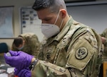 Capt. Cesar Allen, medical officer with the 3rd Civil Support Team (Weapons of Mass Destruction), Pennsylvania National Guard, prepares a dose of the Moderna COVID-19 vaccine on Jan. 13, 2021, at Fort Indiantown Gap, Pa.