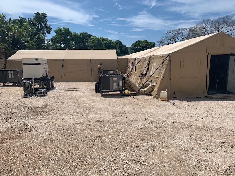 Two tan tent structures with support equipment outside are set up in a dirt field.