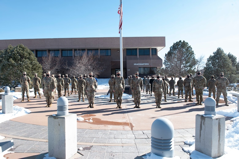 Group of Space Force personnel standing in formation outside around a flagpole.