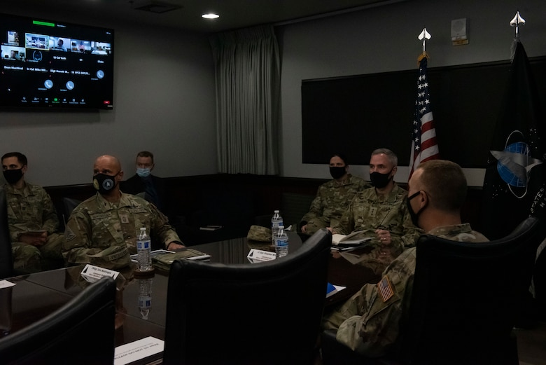 Group of Space Force personnel sitting at conference table during a briefing.
