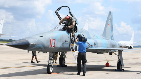 A pilot is assisted in exiting a small fighter jet