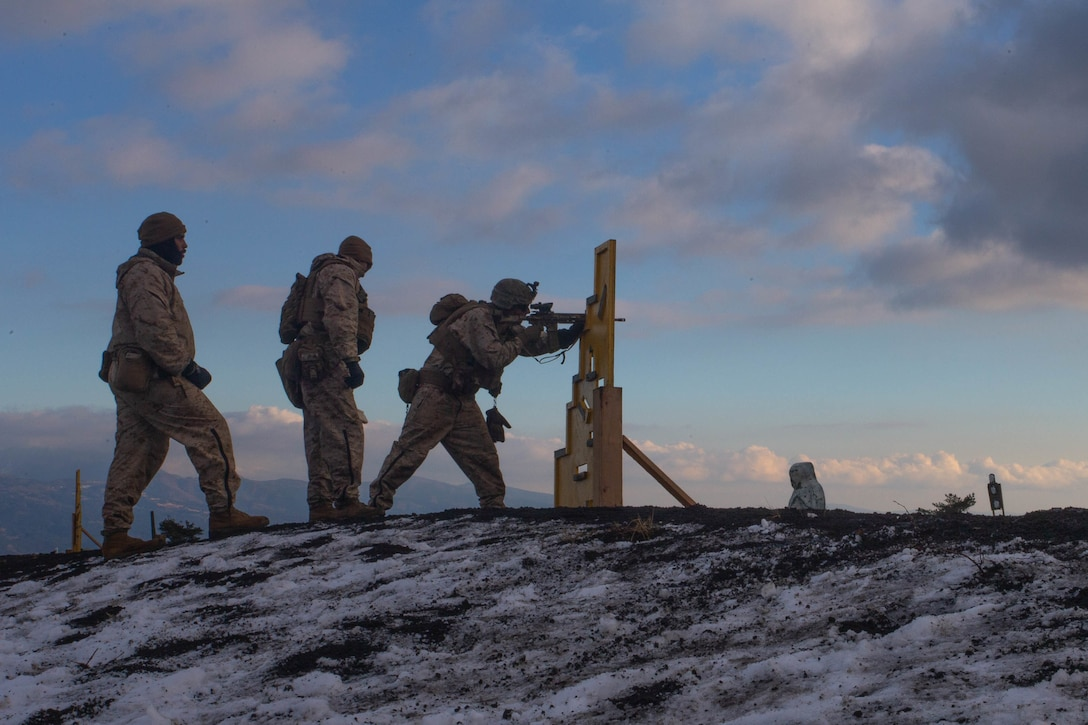 A Marine fires a gun while two others stand behind him.