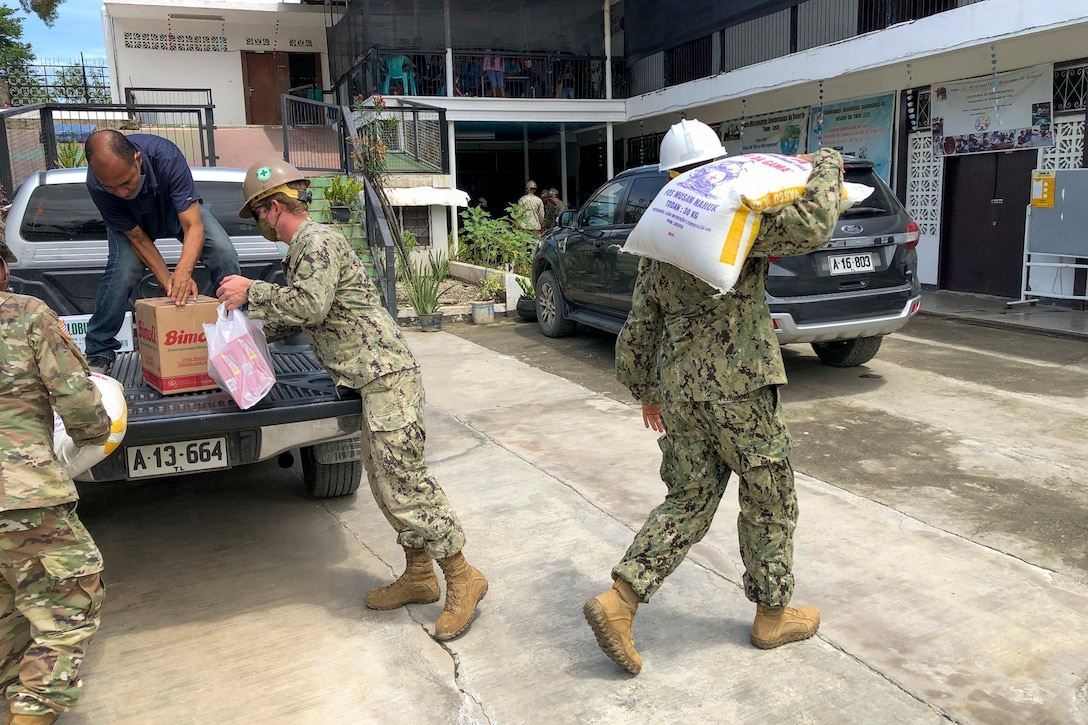 Seabees unload and  carry large bags of food across a street.