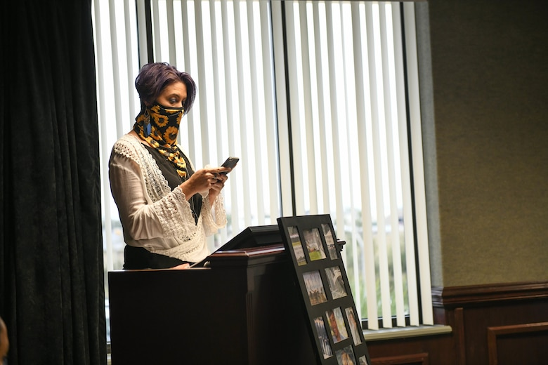 A woman stands at a podium, reading a speech from her phone.