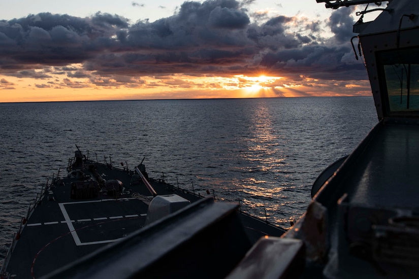 The sun hits the horizon on the ocean as  seen from a ship.