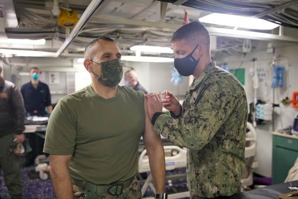 Col. Brian Duplessis, deputy commander, Expeditionary Strike Group (ESG) 2, receives the COVID-19 vaccination aboard the amphibious transport dock ship USS San Antonio (LPD 17), Jan. 11, 2021.