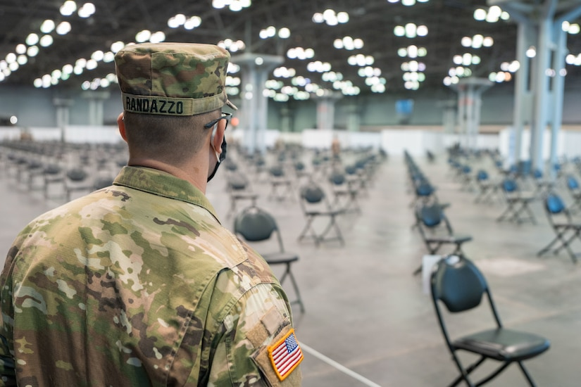 A soldier stands in a large room filled with chairs.