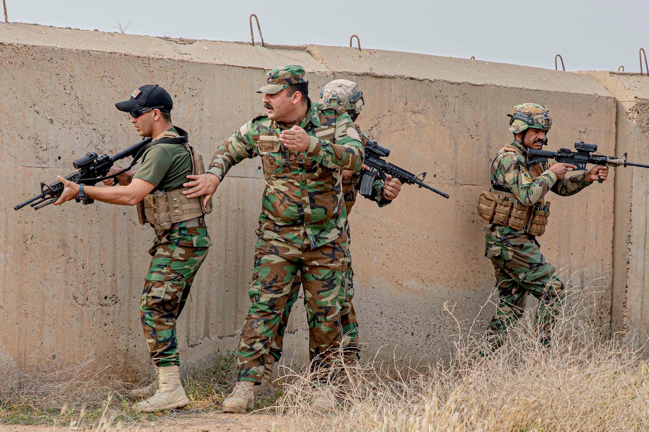 Four service members, three carrying weapons -- proceed around a bunker.