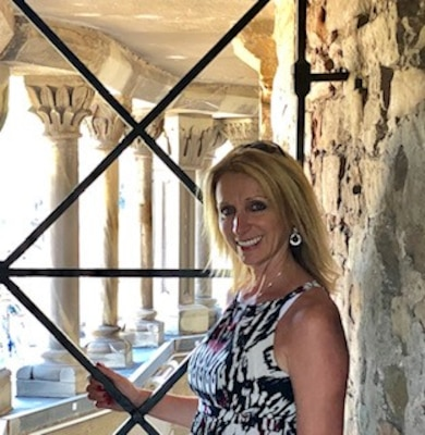 Blonde woman standing next to an exterior wall with columns in the background.