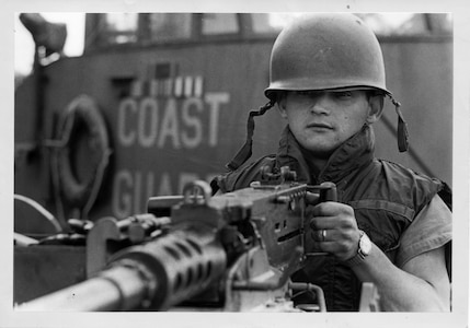 """Coast Guard Gunner's Mate William """"Bill"""" Wells, II, mans one of CGC POINT GLOVER's .50 caliber machine guns for a Navy photographer during the turnover of the cutter to the South Vietnamese Navy in the fall of 1969 in DaNang, South Vietnam."""
