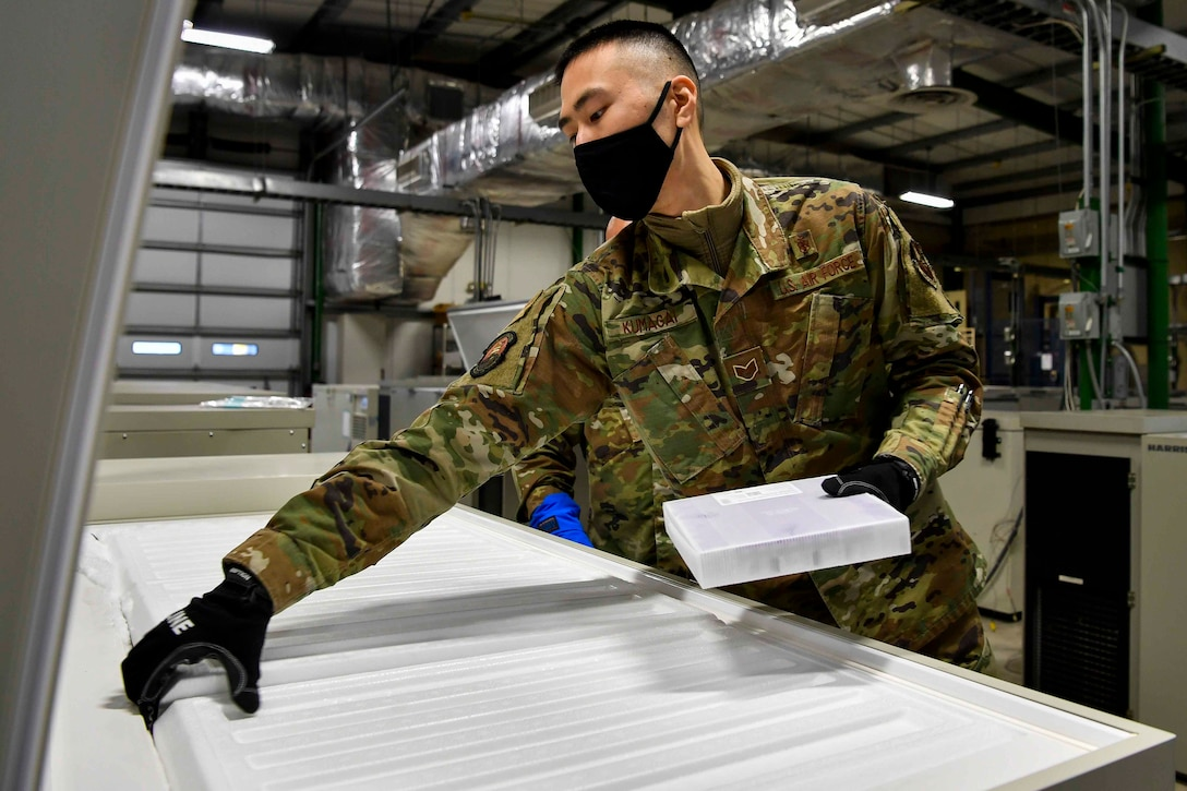 An airman wearing a face mask holds onto a white box while opening a freezer.