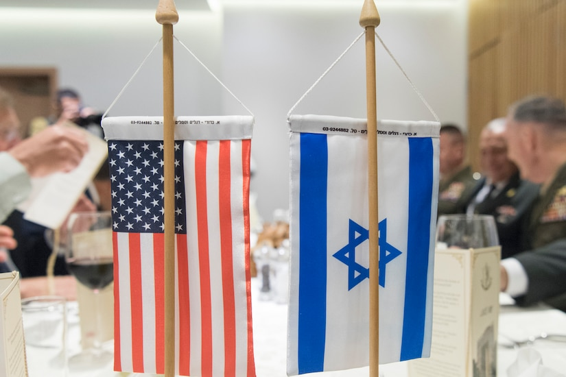 Small U.S. and Israeli flags are on stands that sit on a conference table.