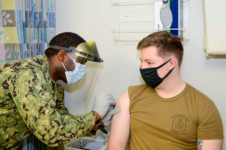 A sailor gives an injection to another sailor.