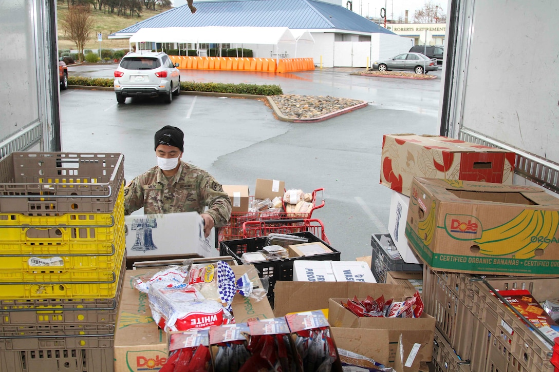 A soldier wearing a face mask sorts through crates of food at the back of a vehicle.