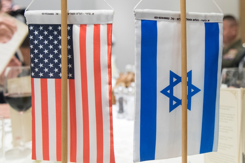 Small U.S. and Israeli flags are on stands that sit on a conference table