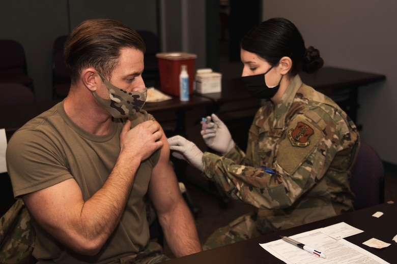 A masked Airman  administers the COVID-19 vaccine to another Airman.