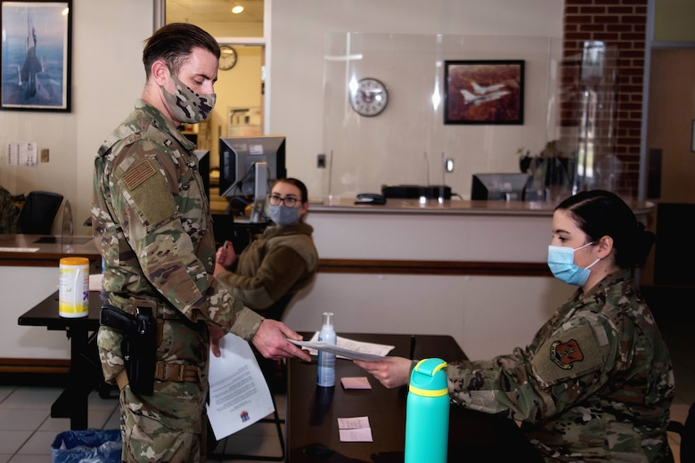 A masked Airman in camouflage fatigues hands COVID-19 screening paperwork to another Airman.