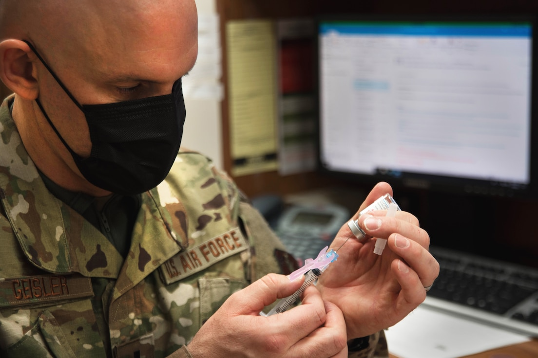 A masked Airmen in camouflage fatigues uses a syringe to extract the COVID-19 vaccine from a small vial.