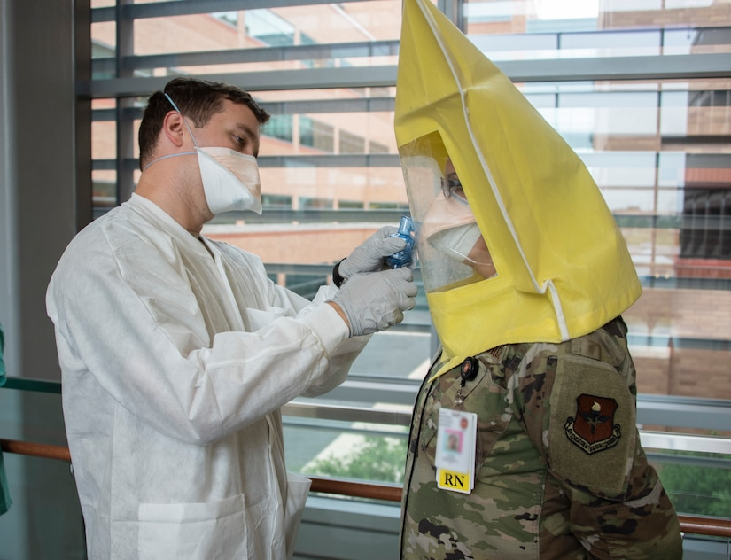 A soldier conducts a respirator fit test for an airman.