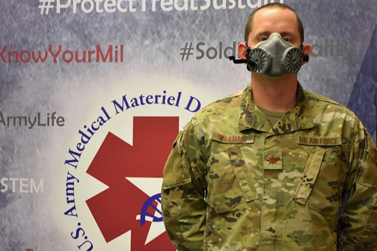 An airman demonstrates the fit of an N95 respirator.