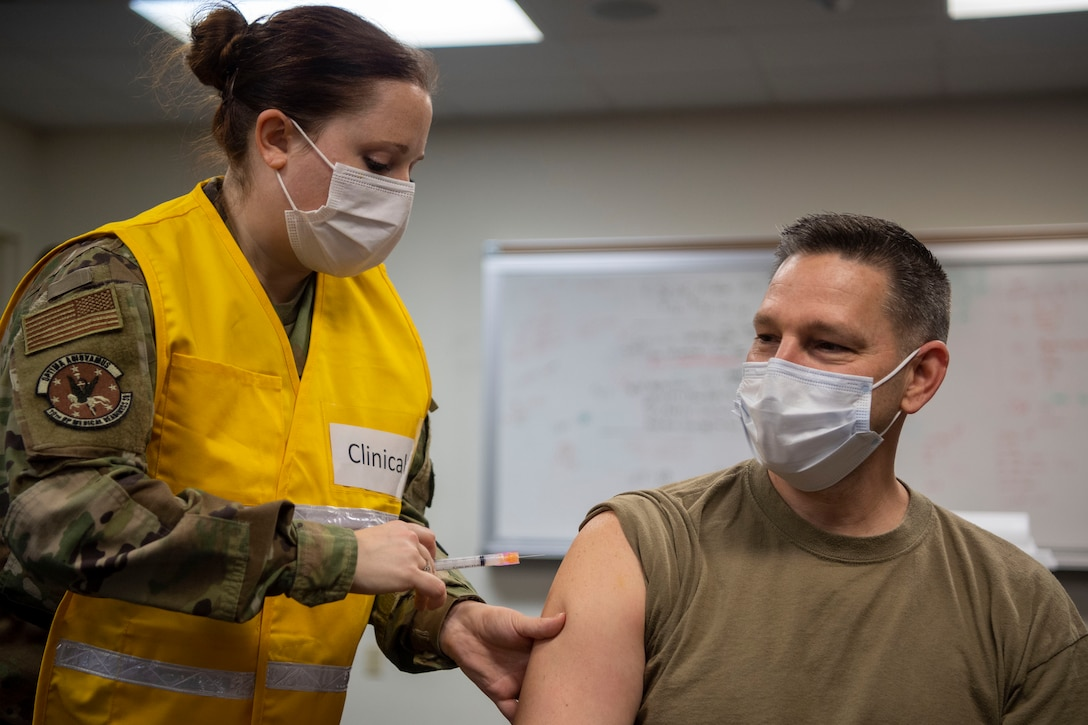 The 19th Medical Group superintendent receives the COVID-19 vaccine from a medical technician.