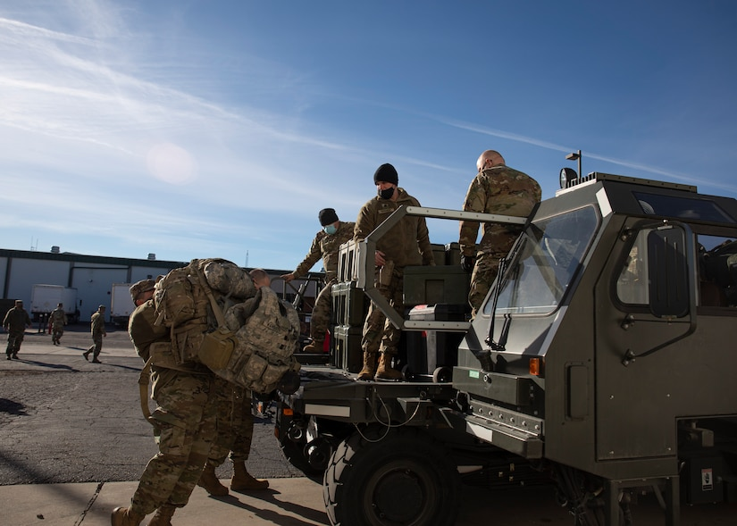 Soldiers load bags.