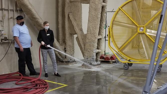 Woman sprays a hose