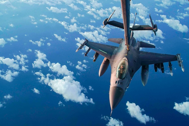 A fighter jet is refueled in midair.