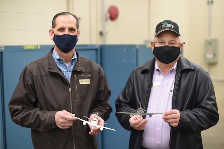 Two men hold miniature planes