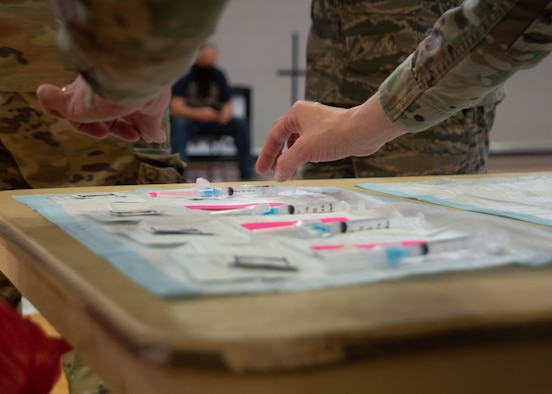 A military member placing syringes on a table.