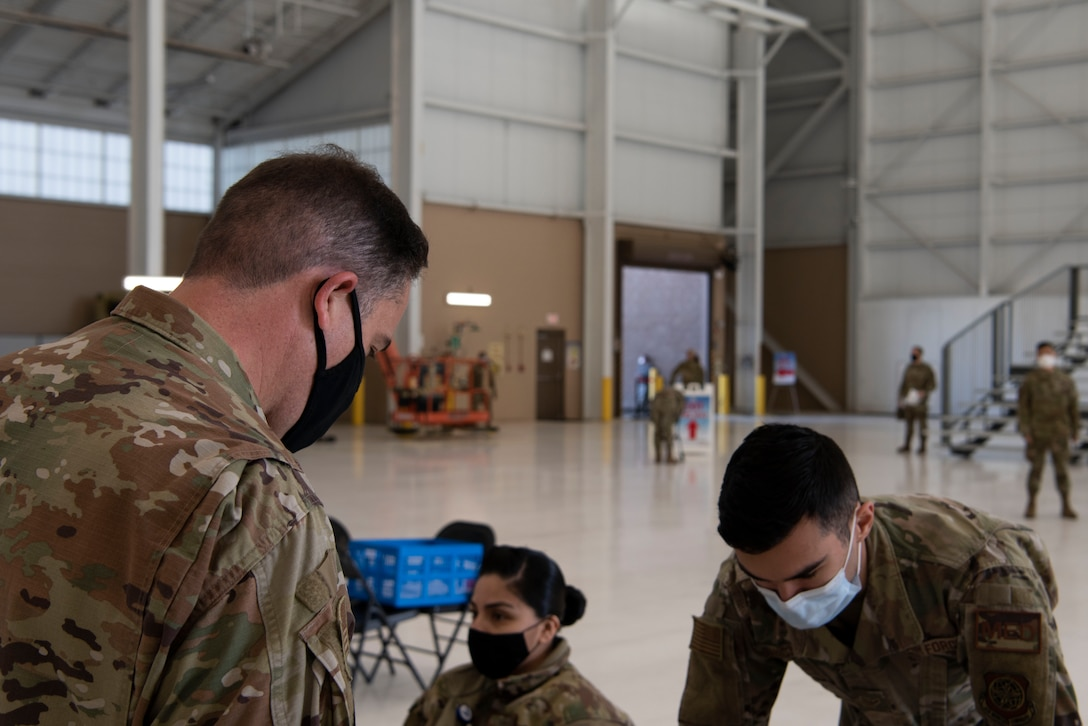 U.S. Air Force Airman 1st Class Tyler Lancaster, 60th Healthcare Operations Squadron medical technician, facilitates patient check out for Lt. Col. Glenn Cameron, 60th Civil Engineering Squadron commander, after Cameron received the influenza vaccine at the point of distribution in a hangar Jan. 14, 2021, at Travis Air Force Base, California. The POD is an organized way of efficiently distributing a vaccine to a large amount of people and preparing medical personnel for future large-scale distributions such as the COVID-19 vaccine. (U.S. Air Force photo by Airman 1st Class Alexander Merchak)
