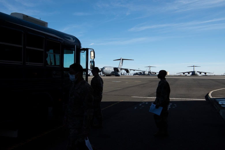 U.S. Airmen board a bus to travel from the influenza vaccine point of distribution in a hangar Jan. 14, 2021, at Travis Air Force Base, California. The POD is an organized way of efficiently distributing a vaccine to a large amount of people and preparing medical personnel for future large-scale distributions such as the COVID-19 Vaccine. (U.S. Air Force photo by Airman 1st Class Alexander Merchak)