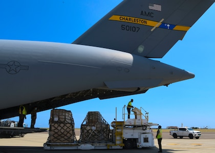 Two people stand on aircraft loading equipment, one above and one behind, ready to load the airplane from the rear. A view of the large rear section of a C-17 is in the shot as well.