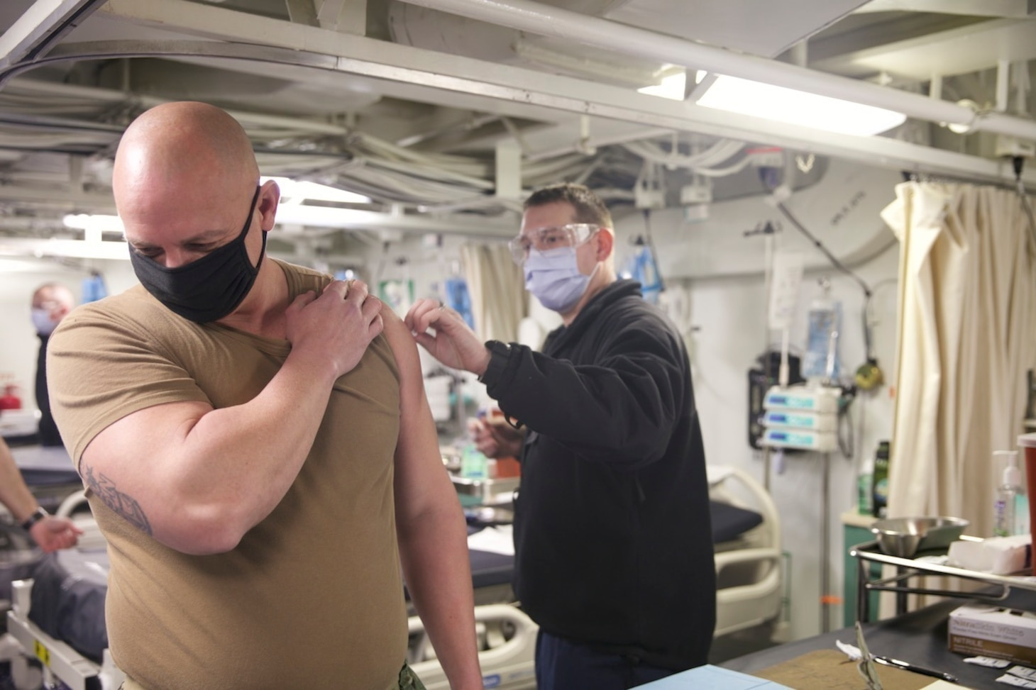 Command Master Chief Todd Mangin, command master chief for Expeditionary Strike Group (ESG 2), receives the COVID-19 vaccination aboard the amphibious transport dock ship USS San Antonio (LPD 17), Jan. 11, 2021.