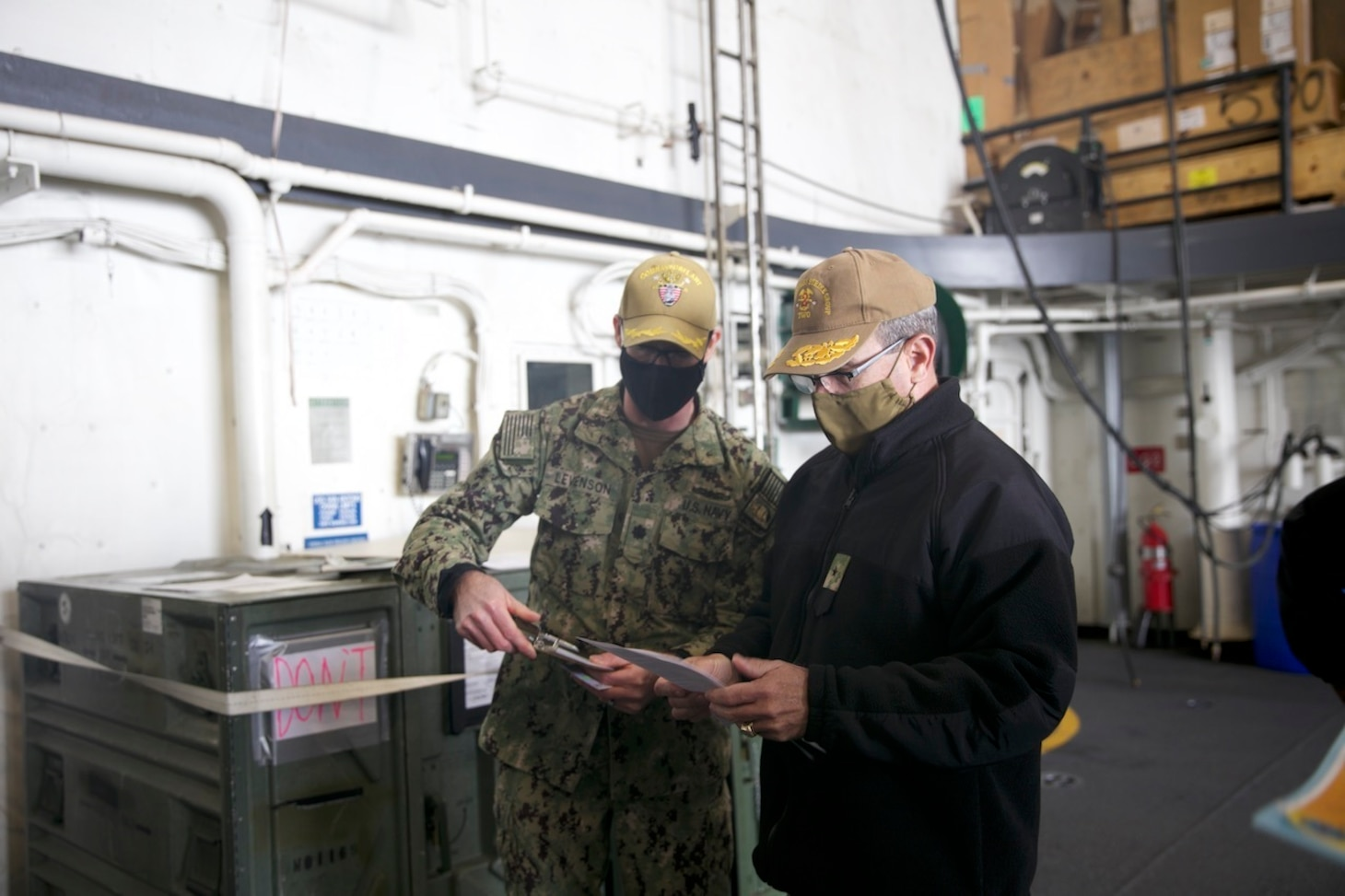 Rear Adm. Robert Katz, commander, Expeditionary Strike Group (ESG 2), reviews paperwork aboard the amphibious transport dock ship USS San Antonio (LPD 17) before receiving the COVID-19 vaccination, Jan. 11, 2021.
